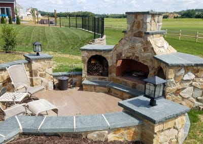 Outdoor fireplace with wood boxes and tile patio