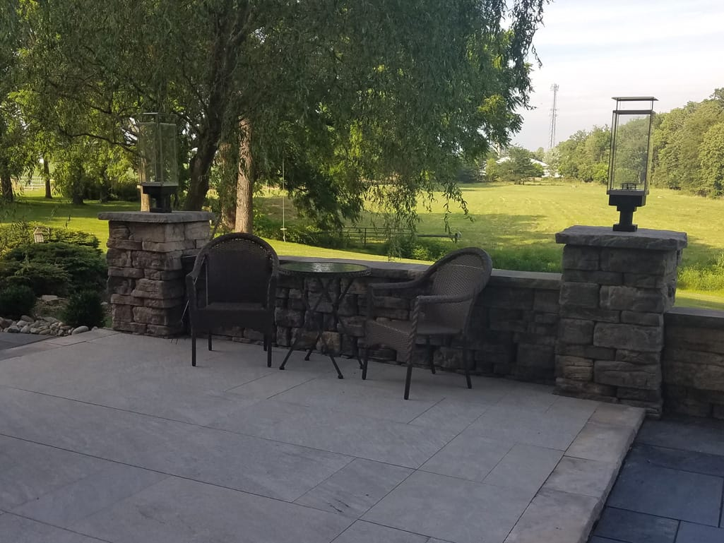Quarziti stone finish patio in waterfall with Belvedere wall and torch lamps