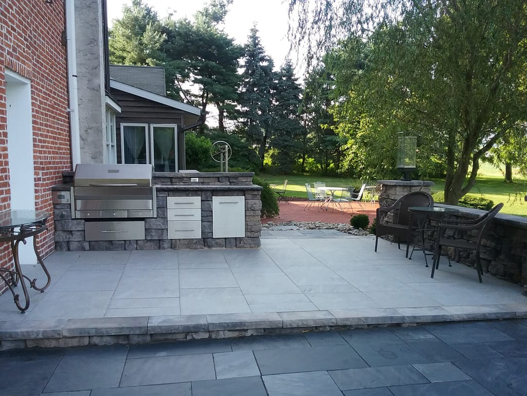 Outdoor kitchen space with Quarziti stone finish tile patio in waterfall
