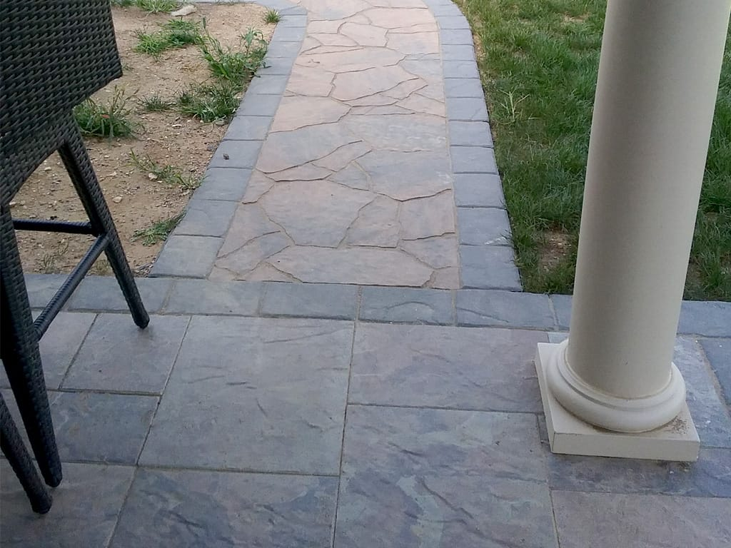 Close up of textured Bella Mega-Arbel walkway with Lafitt charcoal border
