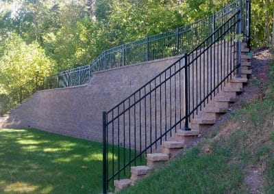 Large retaining wall with mounted aluminum fence